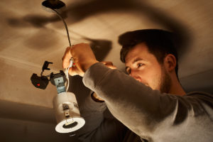 an electrician wires up an LED downlight, lit starkly by a builder's worklight