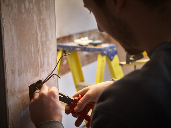 closeup of an electrician stripping wires coming out of a cavity in a plastered wall