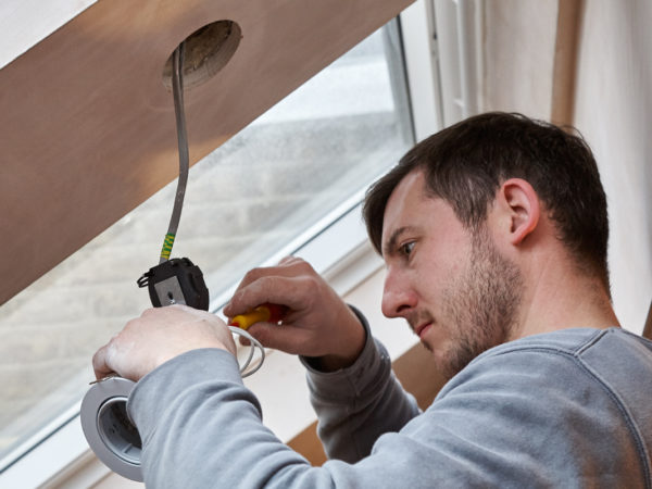 closeup of an electrician wiring an LED spotlight to be mounted in a pre-made hole in a pitched ceiling