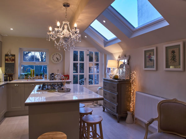 Feature lighting in a Victorian kitchen extension including LED spotlights, a chandelier and counter-top LED strip lighting.
