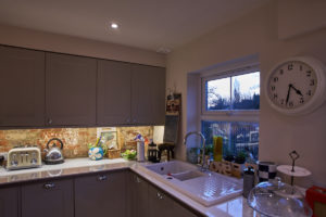 Victorian kitchen extension with counter-tops lit by LED strip-lighting