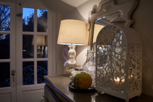 homely setting with warmly lit lamp and ornaments on a table with twilight visible through a window