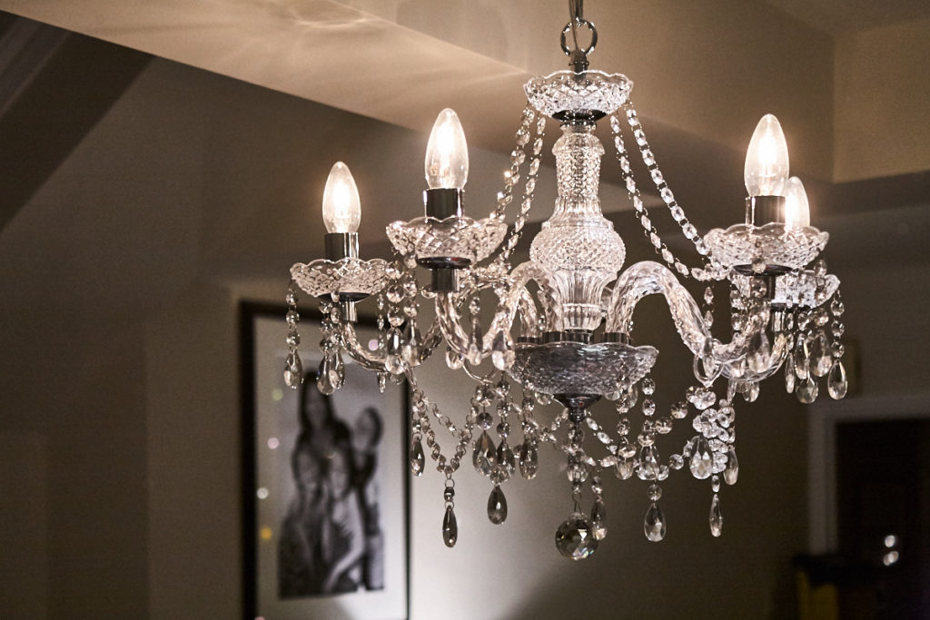 lit chandelier in front of a dark wall with an out-of-focus family photo